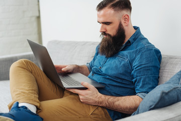 Bearded man sitting on sofa with laptop
