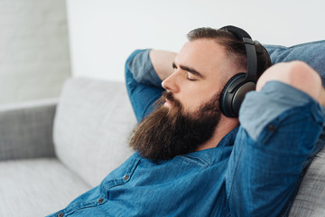 Bearded man listening to music on headphones