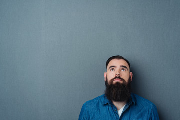 Bearded young man looking up to blank copy space