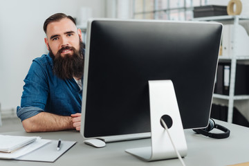 Smiling bearded man sitting in front of monitor