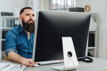 Young bearded man sitting in front of monitor
