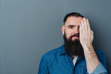 Bearded man covering one eye with his hand