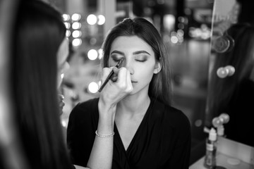 Professional makeup artist working with beautiful young woman. Fashionable Female Model With Soft Skin, Perfect Makeup And Fake Eyelashes. High Resolution
