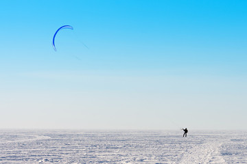 Kitesurfer riding the parachute in the wind among the snow in winter.
