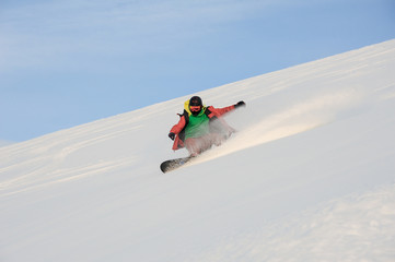 Active snowboarder riding down the snowy slope