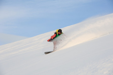 Professional snowboarder riding down the snowy slope