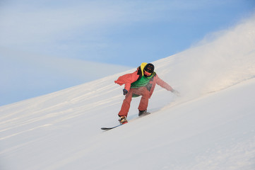 Active snowboarder riding on the snowy slope