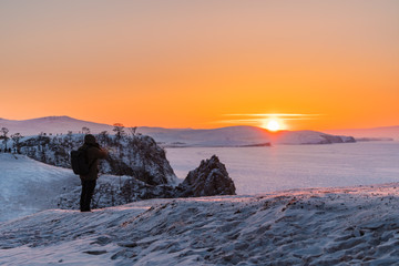 Photographer taking photo of sunset landscape in winter at lake Baikal, Russia. Travelling in winter
