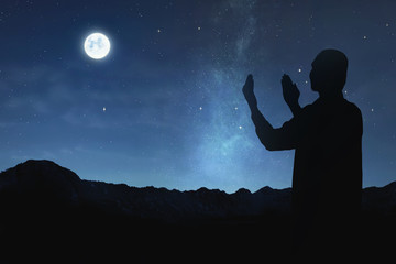 Silhouette of muslim man raising hand and praying to god