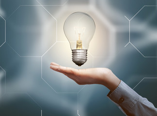 Human hands holding light bulb with abstract background