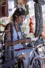 Portrait of a young woman, carding wool at a street market