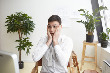 Puzzled male designer gesturing in panic, staring at computer screen, having shocked worried look as he can't make it to finish drawing of construction plan in time. Deadline and stress at work