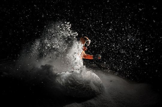 Freeride snowboarder jumping in snow at night