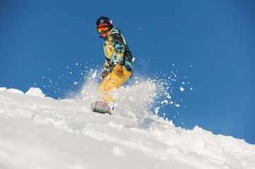 Bottom view of freeride snowboarder sliding down the slope