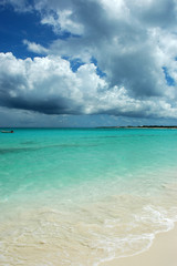Horizontal view of tropical turquoise Caribbean sea, white sand, and heavy stormy clouds. Copy space, tranquil atmosphere of a popular vacation destination, holiday paradise, secret beach