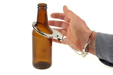 Main d'homme menottée à une bouteille