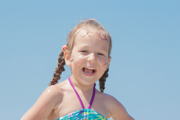 Close-up outdoors beach portrait of laughing happy little girl kid