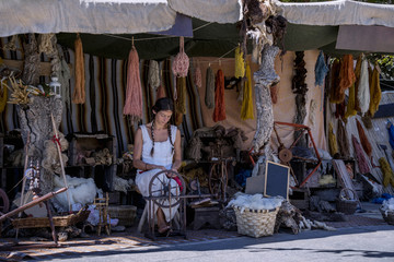 Woman using a spinning wheel, in a street market