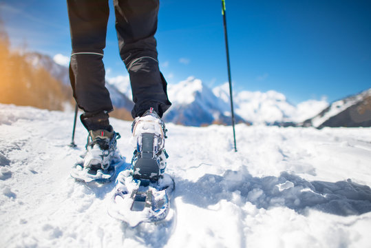 Walk with snowshoes in the snow during mountain holidays