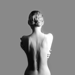 Art Nude fashion Nude back of blonde woman on grey background. Girl hugs herself with her hands