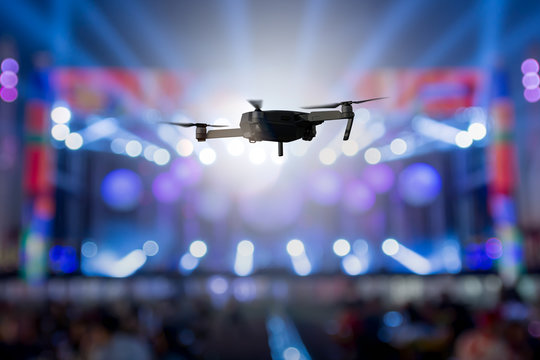 flying drone recording event by video camera at night concert