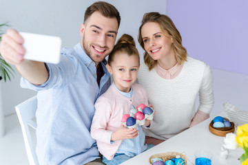 Family taking selfie with Easter painted eggs