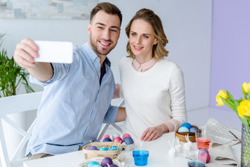 Young man and woman taking selfie while painting Easter eggs