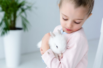 Child girl holding white rabbit