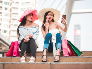 Two beautiful young women sitting on the stairs and making self-portrait by smart phone after enjoying in shopping