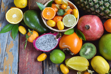 Mix of ripe tropical fruits with avocado mango, kumquat, kiwi, citrus. Superfood background. Vegetarian raw food. Copy space