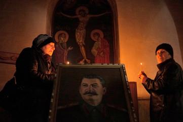 Women light candles behind a portrait of Stalin inside a church in Gori