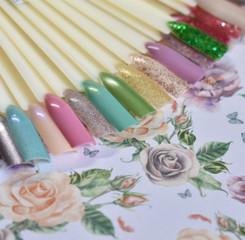 Nagellack-Präsentation: Nagellack in verschiedenen Faben an Blumenuntergrund