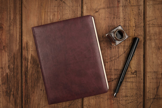 A leather bound journal, and ink well and pen