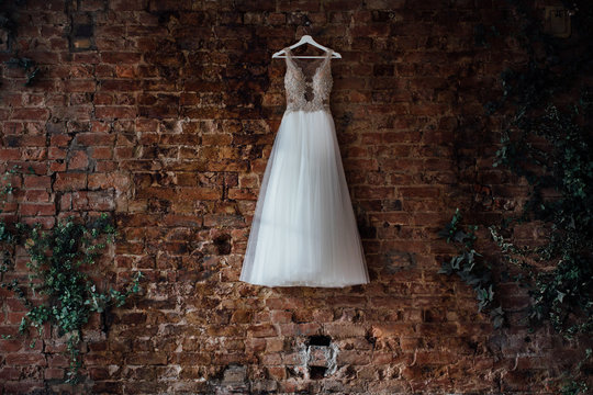 beautiful bridal wedding dress hanging on a hanger on a brick wall in a loft studio. No one.