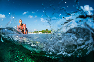Happy surfer rides the clear ocean wave and smiles at camera. Split shot with underwater view of the coral reef and lot of splashes