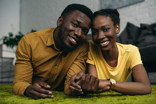 beautiful young african american couple lying on carpet and smiling at camera