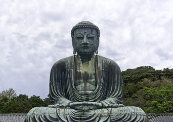 Famous monumental outdoor bronze statue of Amida Buddha at the entrance of the buddhist temple of Kōtoku-in, in the city of Kamakura, Japan. One of the most famous religious statue in Japan