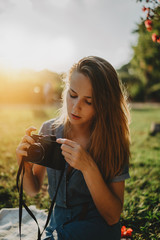 Beautiful young hipster girl with freckles using vintage film camera outside, pretty woman with long hair taking photo on retro camera in sunny city park while enjoying her weekend