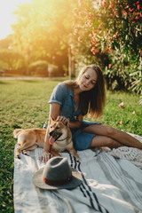 Beautiful young smiling girl sitting at sunny city park with dog enjoying holidays, pretty woman with long hair chilling with shiba inu dog at park, lifestyle holidays concept