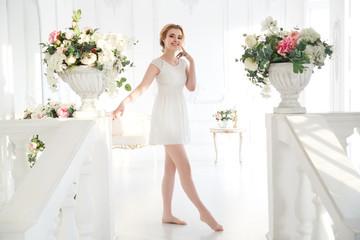 Beautiful joyful bride in a short dress in full growth in a light solemn interior.