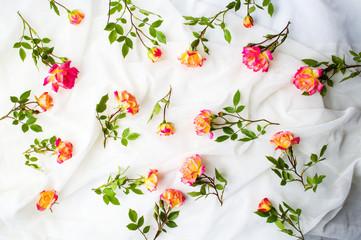 Orange roses on white fabric flatlay