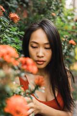Sensual woman standing at blooming bush