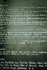 Menu card with starters, main courses, cheese and desserts written by hand in French on chalk board at a restaurant in Strasbourg, Alsace, France