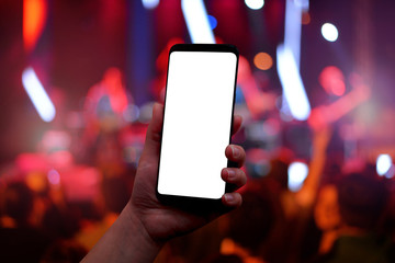 Mobile phone in hand with isolated screen for mockup. Music concert red lights and crowd in background.