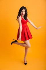 Full length portrait of fascinating woman with red lips smiling and posing in short fashion dress, isolated over yellow background