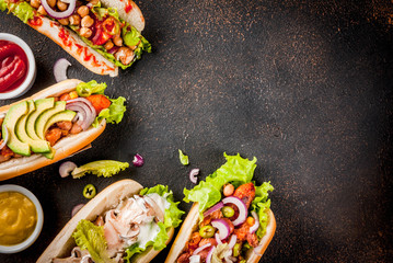 Assortment of different homemade Vegan Carrot Hot Dogs, with fried onion, avocado, chili, mushrooms, tomatoes and beans, dark rusty background copy space top view