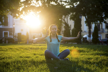 Girl is sitting on the grass with the sunlight yoga 2
