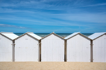 Traditional white wooden beach huts on the beach of Villers, Normandy, France