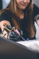 Cropped view of female tattoo artist working with ink