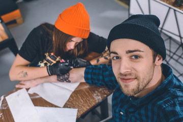 Smiling man and tattoo master during tattoo process in studio